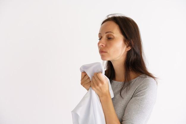 Una graziosa donna caucasica con in mano una camicia profumata bianca e pulita su una parete chiara il concetto di assistenza domiciliare per l'abbigliamento