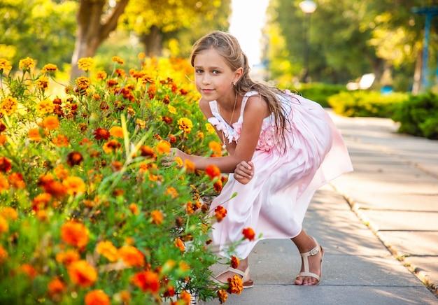 Una ragazza carina e affascinante in un bellissimo vestito rosa annusa calendule infuocate in un parco luminoso in una giornata di sole in una vacanza tanto attesa