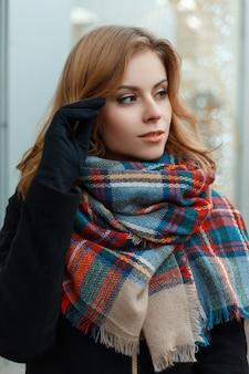 Carina affascinante giovane donna con capelli biondi in un elegante cappotto invernale con una sciarpa di lana vintage in guanti neri in posa