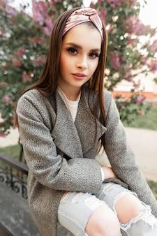 Carina giovane donna affascinante con trucco colorato in bandana alla moda in cappotto elegante grigio resto sulla strada vicino a un albero lilla sbocciante. modello di bella ragazza in abiti primaverili alla moda si rilassa all'aperto.