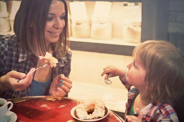 Ragazzo biondo allegro sveglio con il pezzo di dolce e sua madre con la tazza che si siede in caffè