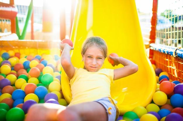 Una ragazza carina e allegra giace nel parco giochi con attrezzature morbide e luminose e lancia palloncini colorati