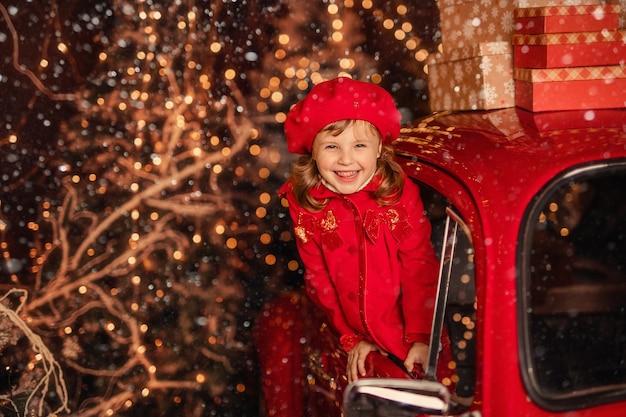 Una ragazza allegra carina vicino a un'auto rossa di natale che cattura la neve con le sue mani
