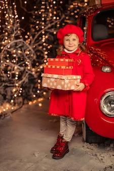 Una ragazza carina allegra in un berretto rosso con i regali di capodanno nelle sue mani vicino a un'auto rossa
