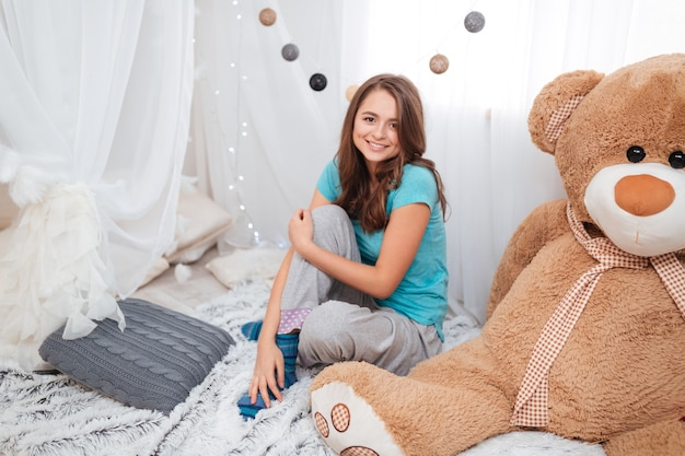Ragazza carina allegra con un grande orso di peluche seduto nella stanza dei bambini a casa