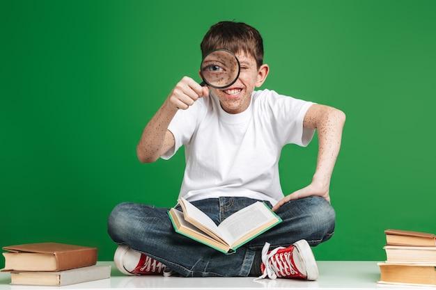 Simpatico ragazzino allegro con le lentiggini che studia, seduto con una pila di libri sul muro verde, con in mano una lente d'ingrandimento