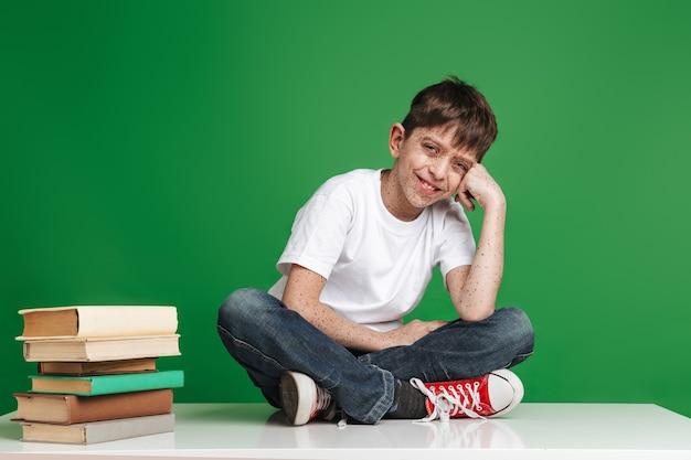 Simpatico ragazzino allegro con le lentiggini che studia, seduto con una pila di libri sul muro verde