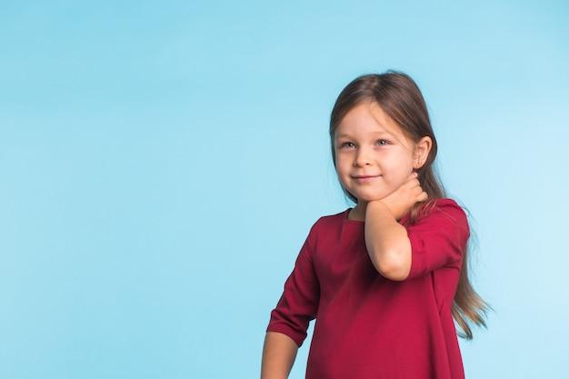 Ritratto di bambina allegra sveglia, isolato sulla parete blu con lo spazio della copia