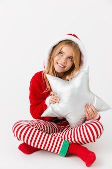 Bambina allegra sveglia che indossa il costume di natale isolato, seduto, tenendo un cuscino