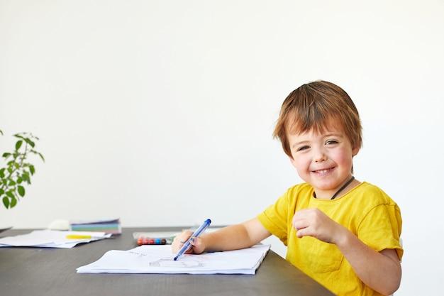 Piccolo ragazzo prescolare allegro sveglio in camicia gialla luminosa che si siede al tavolo e quadro dipinto