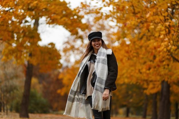 Carina giovane donna allegra in un cappello nero di moda in una giacca vintage con una sciarpa calda viaggia attraverso il parco in autunno sullo sfondo di alberi con fogliame dorato. ragazza con un sorriso positivo all'aperto