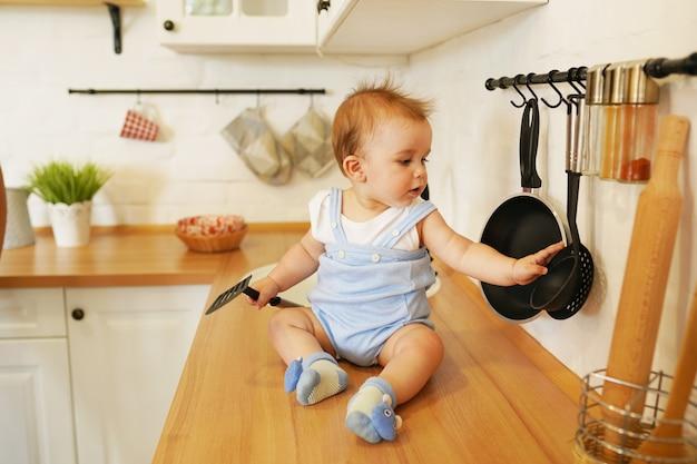 Bambino carino bambino 1 anni seduto sul tavolo con un grosso cucchiaio in cucina