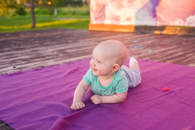 Neonato sveglio del bambino che si trova sulla coperta in giorno di estate sulla natura. picnic in famiglia in un parco.