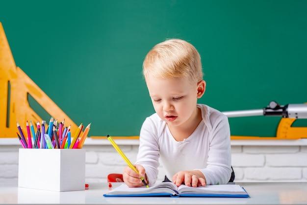 Ragazzo sveglio del bambino in aula vicino al processo educativo dello spazio della copia della lavagna della scrivania della lavagna