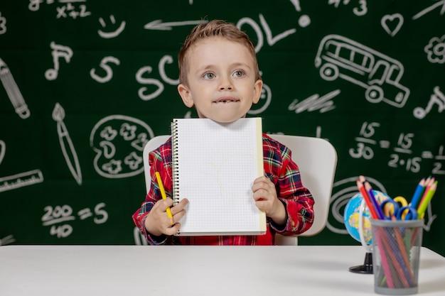 Ragazzo carino bambino facendo i compiti. ragazzo intelligente disegno alla scrivania. scolaro. studente della scuola elementare che disegna nel luogo di lavoro. ai bambini piace imparare. scuola a casa. di nuovo a scuola. ragazzino a lezione di scuola