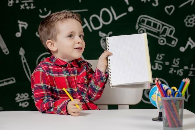 Ragazzo carino bambino facendo i compiti. scolaro. ai bambini piace imparare.