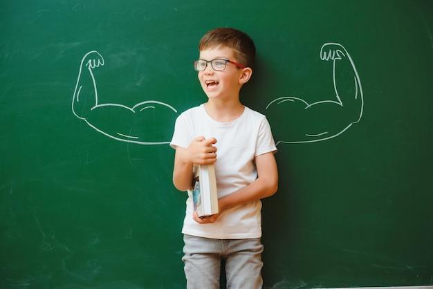 Ragazzo carino bambino in uniforme scolastica e occhiali. vai a scuola per la prima volta. bambino con zaino e libri. ragazzo in aula vicino alla lavagna con i muscoli su di esso. di nuovo a scuola