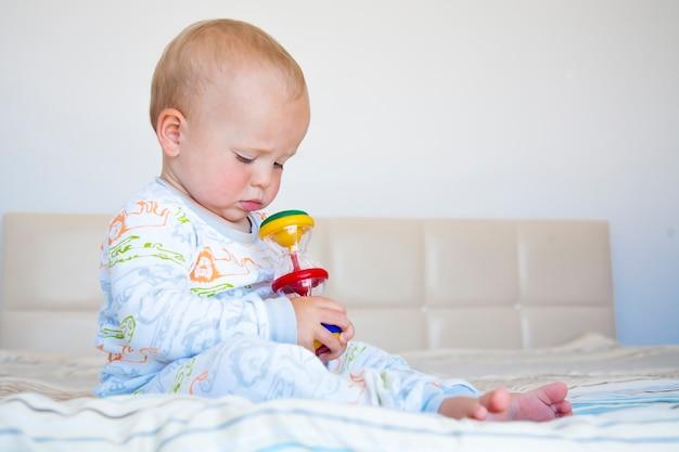 Ragazzo sveglio del bambino che si siede in pigiama sul letto e gioca con il giocattolo colorato.