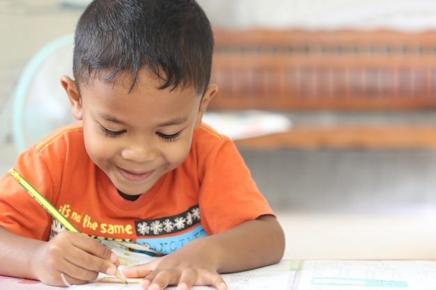Ragazzo carino bambino che studia e pensa a casa.