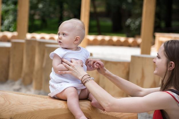 Bambino carino che si diverte nel parco giochi ecologico all'aperto. la mamma tiene dolcemente il bambino.
