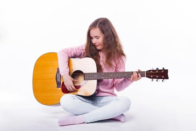 Ragazza sveglia del bambino che gioca alla chitarra acustica sopra bianco