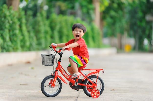 Bambino carino felice con la bicicletta