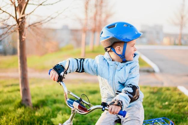 Il bambino carino con il casco impara e va in bicicletta in una giornata di sole al tramonto
