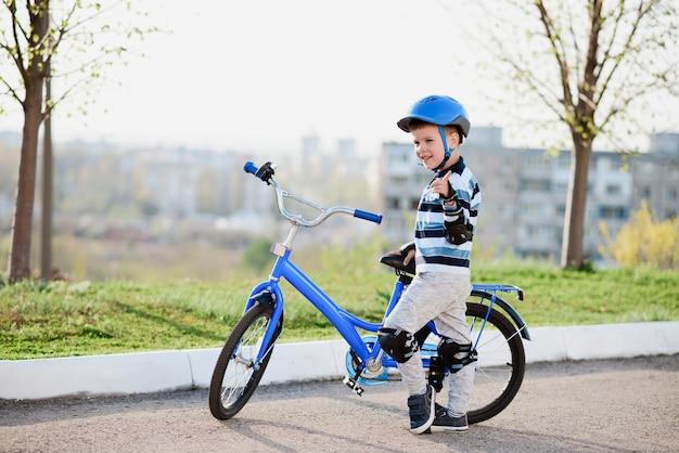 Bambino carino con casco e protezione in piedi vicino alla sua bici