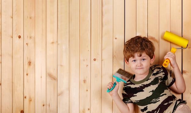 Cute bambino tenere pennelli e andando a fare la riparazione