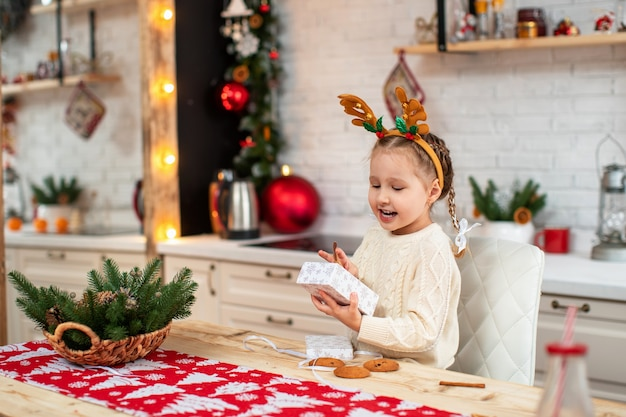 Bambino carino al tavolo della cucina con una scatola
