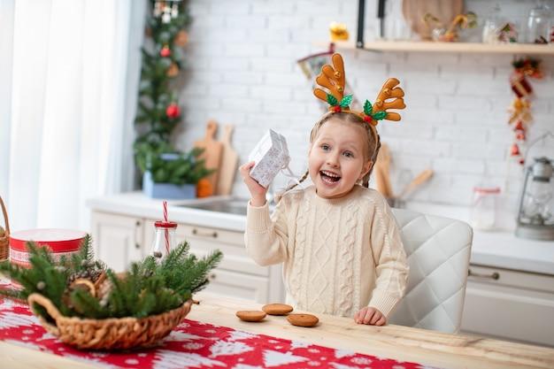 Bambino carino in maglione leggero e fascia con corna di cervo seduto