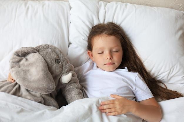 La bambina carina dorme nel letto con un elefante giocattolo.