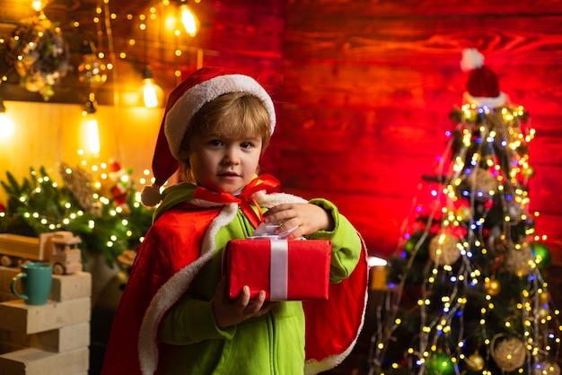 Bambino sveglio che apre un regalo di natale. ragazzino allegro vestito da babbo natale. un ragazzo con un cappello da babbo natale aiuta con il regalo di natale in una scatola rossa.