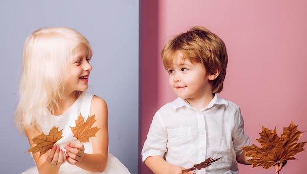 Bambino carino gioca con foglia. foglia caduta foglie isolate. autunno copia spazio tendenza e moda di caduta delle foglie