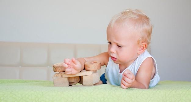 Bambino sveglio che gioca con una macchina di legno.