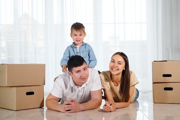 Il bambino carino si siede sulla schiena del padre sdraiato sul pavimento leggero nella nuova casa vicino alla bella moglie tra scatole di cartone