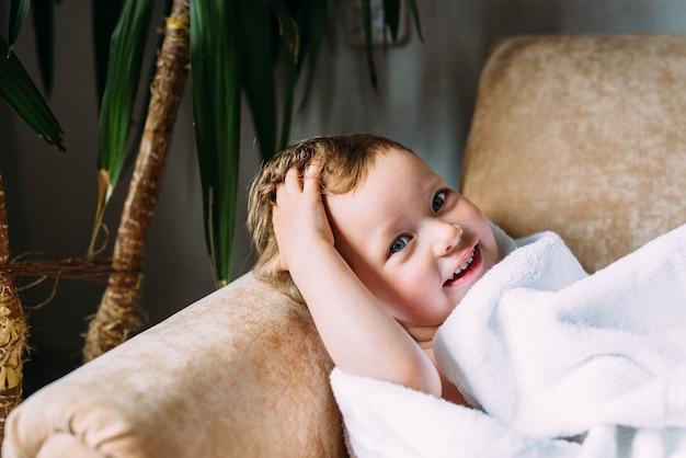 Bambino carino con gli occhi azzurri avvolto in un asciugamano bianco