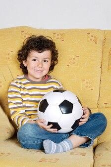 Bambino carino con un pallone da calcio sul divano di casa