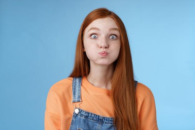 Carina fanciullesca giocosa affascinante rossa ragazza schioccare gli occhi azzurri fissando la fotocamera trattenere il respiro inalare la bocca d'aria in piedi promessa senza parole non scivolare segreto recitazione immaturo in piedi divertente felicemente