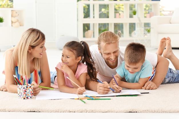 Bambini svegli che disegnano con i genitori a casa