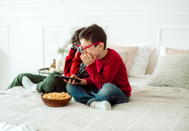 Bambini svegli che mangiano popcorn mentre guardano la tv a casa in 3 bicchieri d.