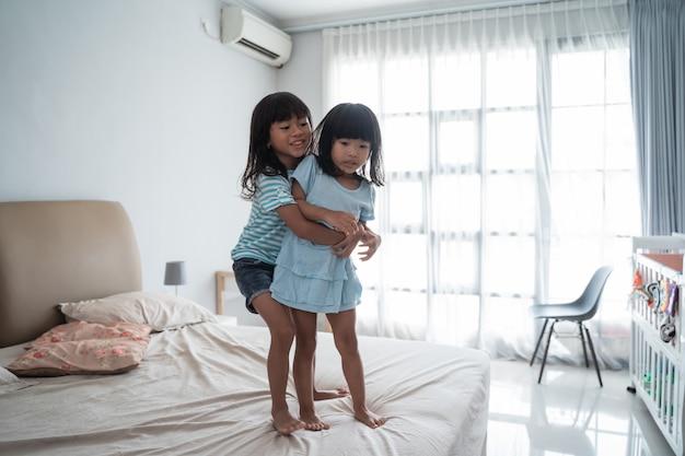 Ragazza sveglia dei bambini che gioca sul letto