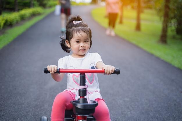 Bambini carini in sella a una bicicletta. bambini che si godono un giro in bicicletta.
