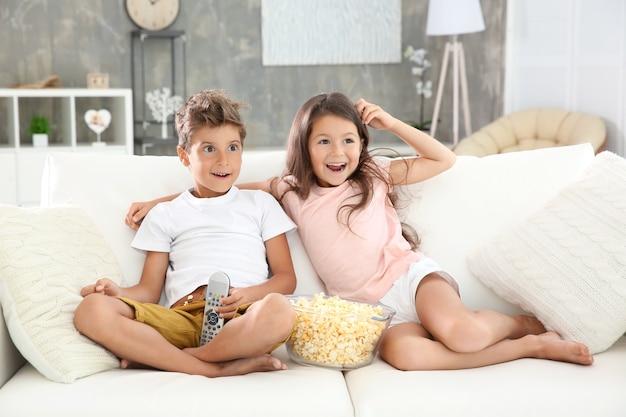 Bambini carini che guardano la tv sul divano di casa