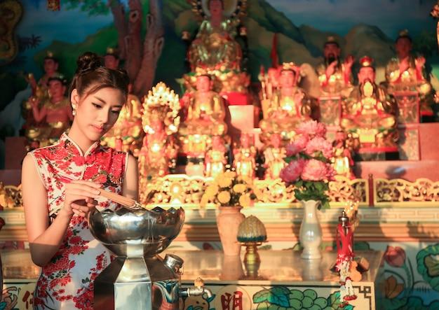 Carina ragazza cinese che veste tradizionale vestito rosso cheongsam che brucia bastoncini di incenso e paga rispetto e prega al dio cinese per fortuna