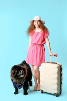 Simpatico cane chow-chow e giovane donna con la valigia sulla superficie del colore