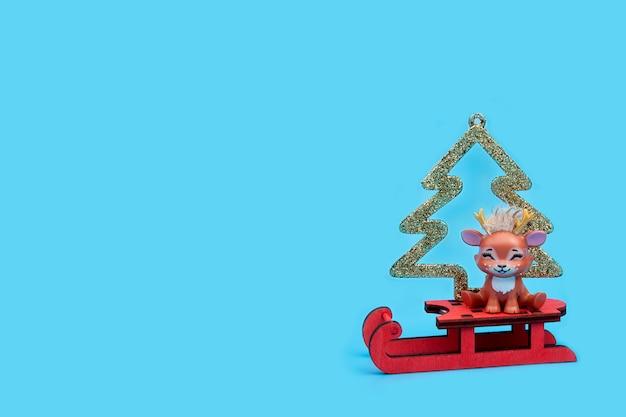 Renne di natale carino con albero di natale dorato seduto su una slitta. concetto di natale, felice anno nuovo. cartolina.