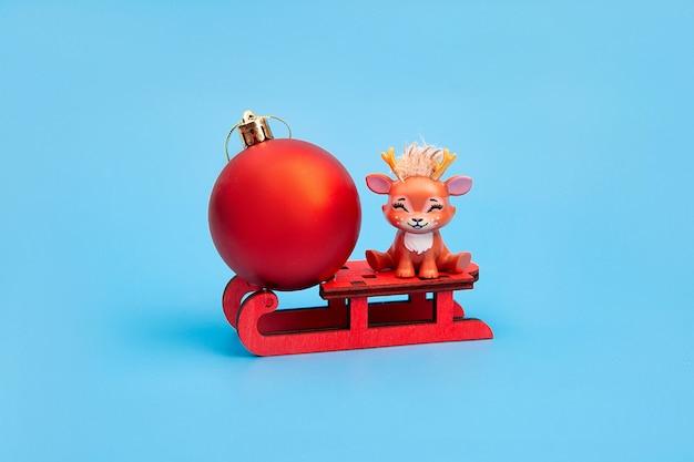 Renne di natale carino con palla rossa di natale seduto su una slitta. concetto di natale, felice anno nuovo. cartolina.