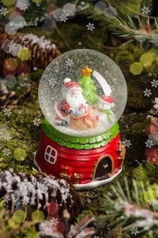 Un simpatico giocattolo di natale, una sfera di neve con babbo natale, un pupazzo di neve e un albero di natale all'interno. idea regalo e arredamento di natale
