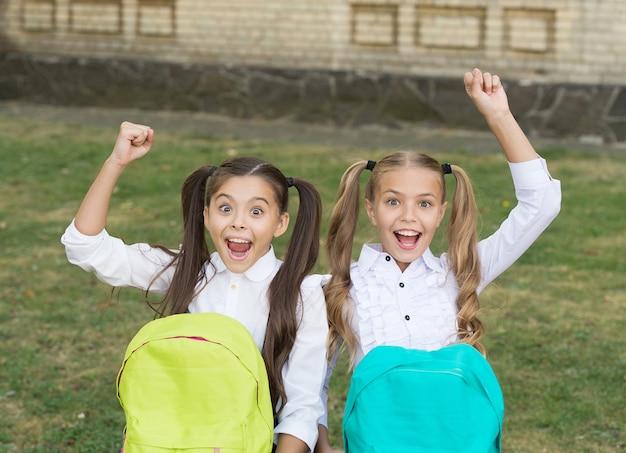 Ragazze carine dei compagni di classe con gli zaini, concetto di infanzia felice.
